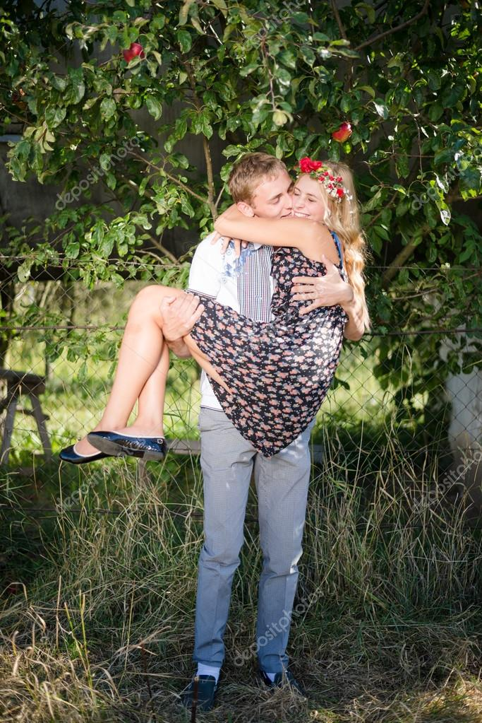 Man carrying woman on arms and hugging outdoors