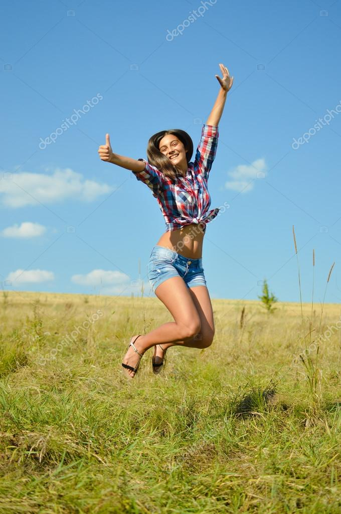 jumping joy: sexy pretty girl in jeans shorts running high and happy smiling on blue sky outdoors copy space background, portrait
