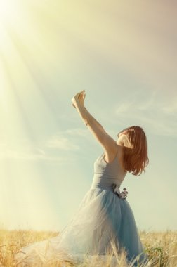 Picture of one young pretty lady having fun standing in the field hands up on blue sky copyspace background