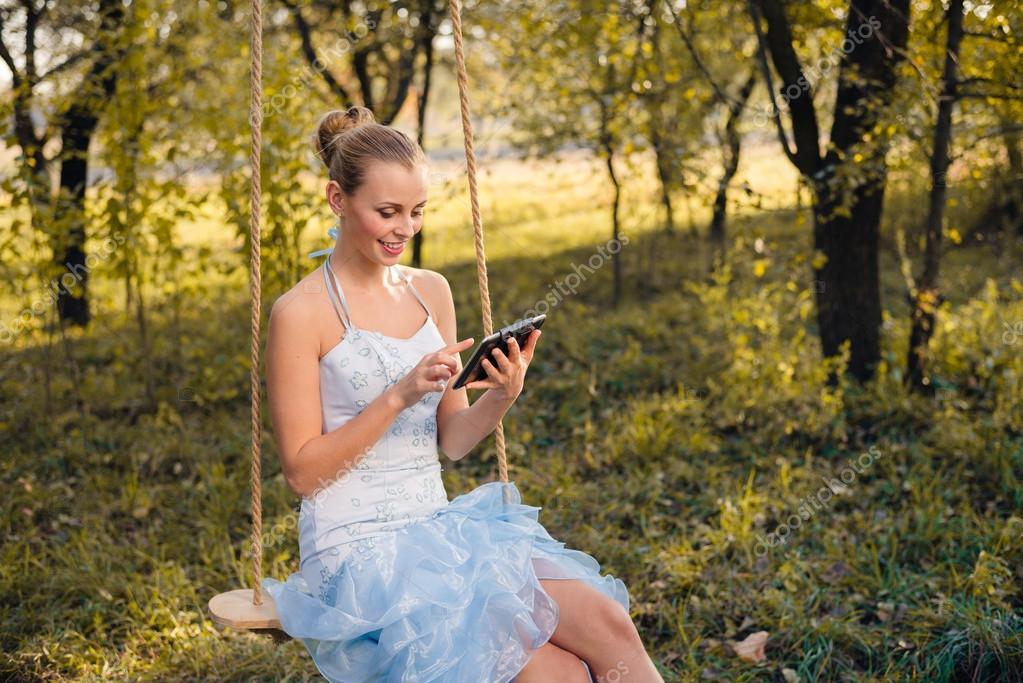 Schöne junge Frau in Prom Kleid sitzt auf Schaukeln und Eingabe auf ...
