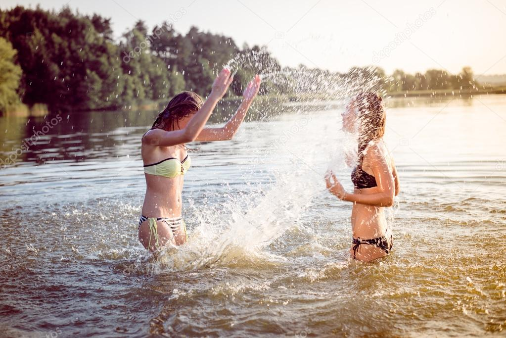 summer fun: filtered image of 2 beautiful young woman or teenage girls best friends having fun and splashing water in river or lake at sunset on sunny outdoors copy space background
