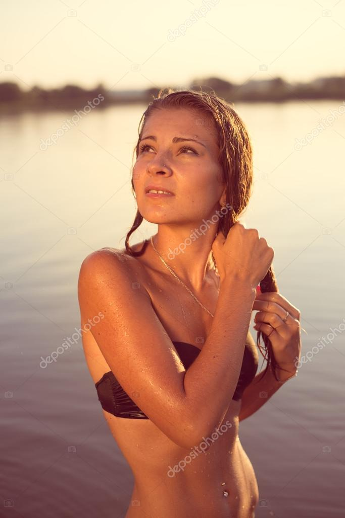 Beautiful sexy woman in black swimsuit with wet hair posing at water body on summer sunset background