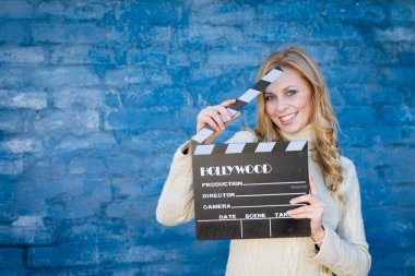 Happy young blond woman in white knitted sweater with cinema clapper board smiling over blue concrete or brick wall copy space background stock vector