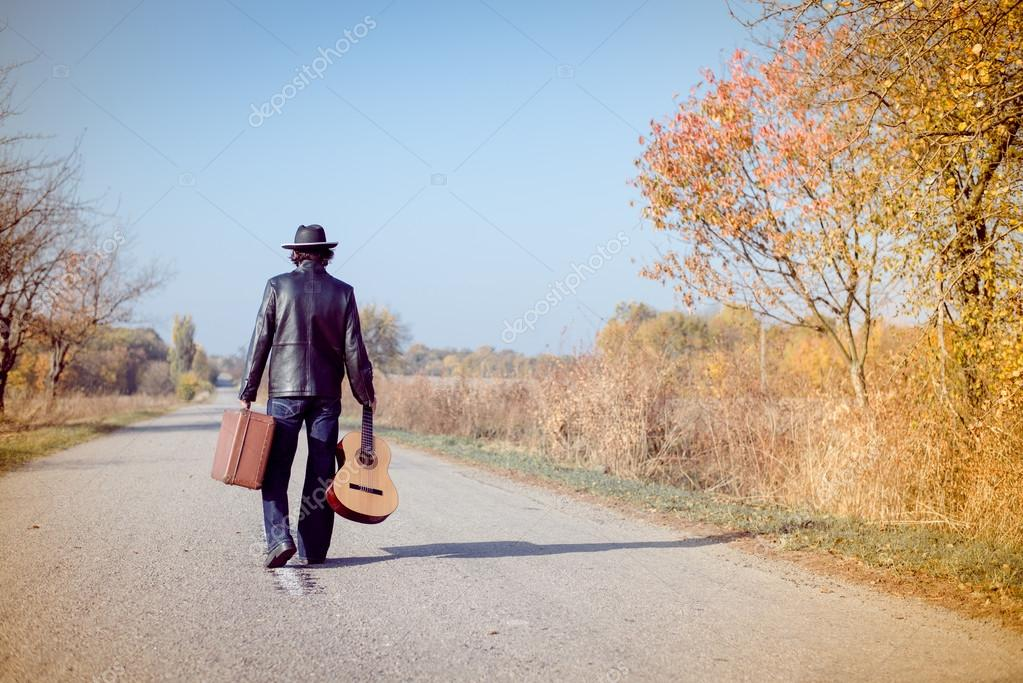 Man with suitcase and guitar