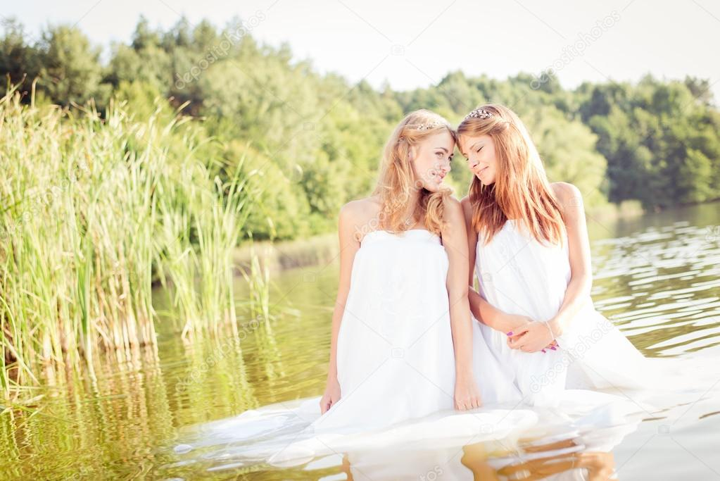 Princesses in white dresses at water