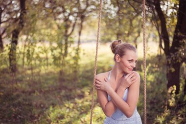 Woman in prom dress sitting on swing