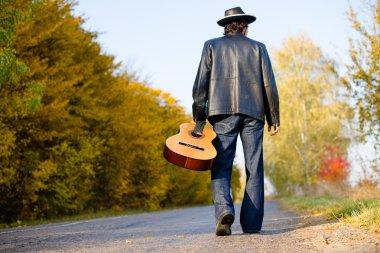 Man holding guitar and walking away