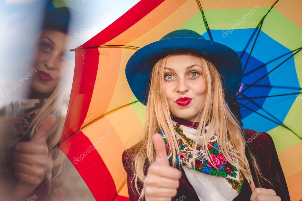Beautiful young woman in hat holding umbrella and blowing kiss