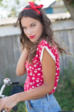 Young beautiful pinup woman cycling in countryside