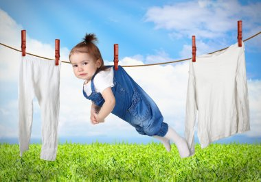 Funny child hanging on line with clothes, laundry creative conce