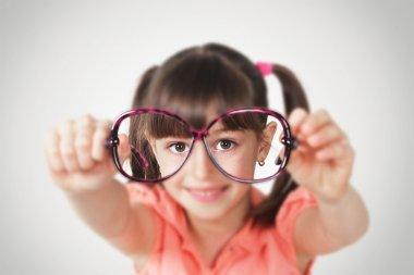 little girl holding eyeglasses, health eyesight concept.Soft fo