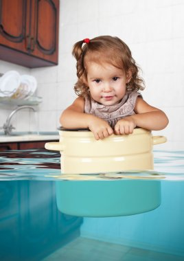 Funny little girl swim in pan in the flooded kitchen, rowdy crea