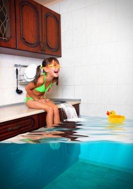 Child girl make mess, flooded kitchen imitating swimming pool, f