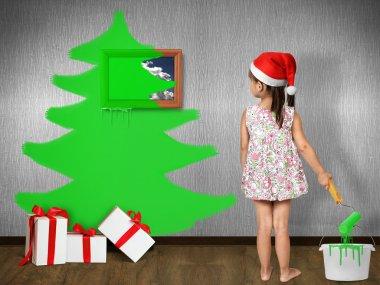 Funny child girl dressed Santa hat, draws Christmas tree on wall