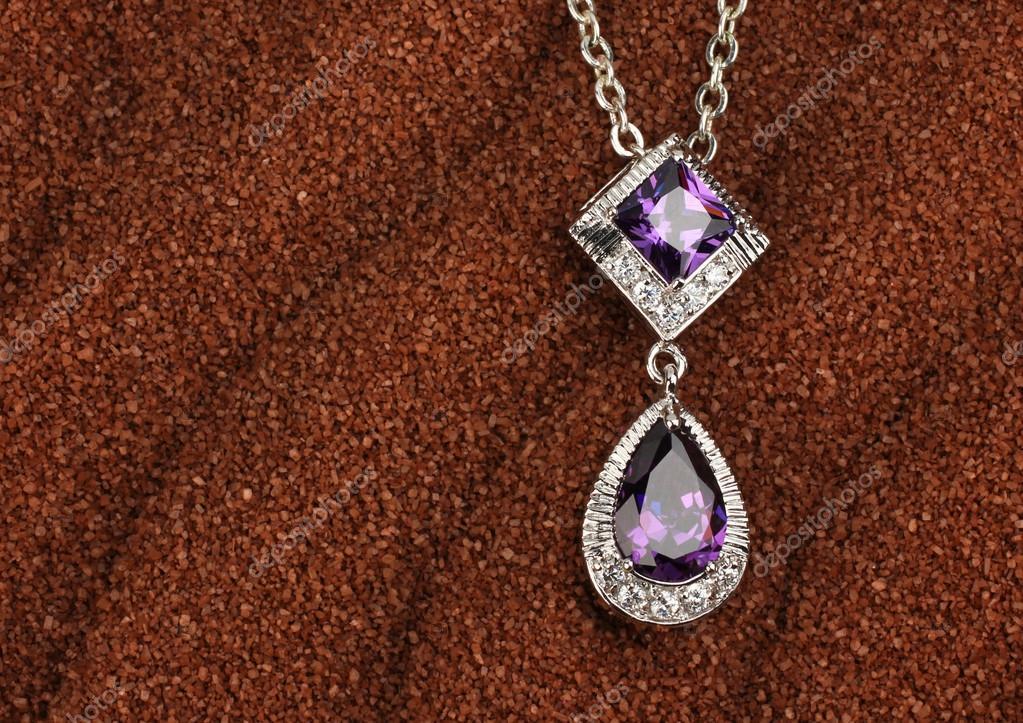 9356d34ca279 joyería colgante con diamantes sobre fondo de arena marrón