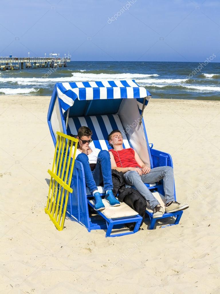 people enjoy sunbath in the roofed wicker beach chair