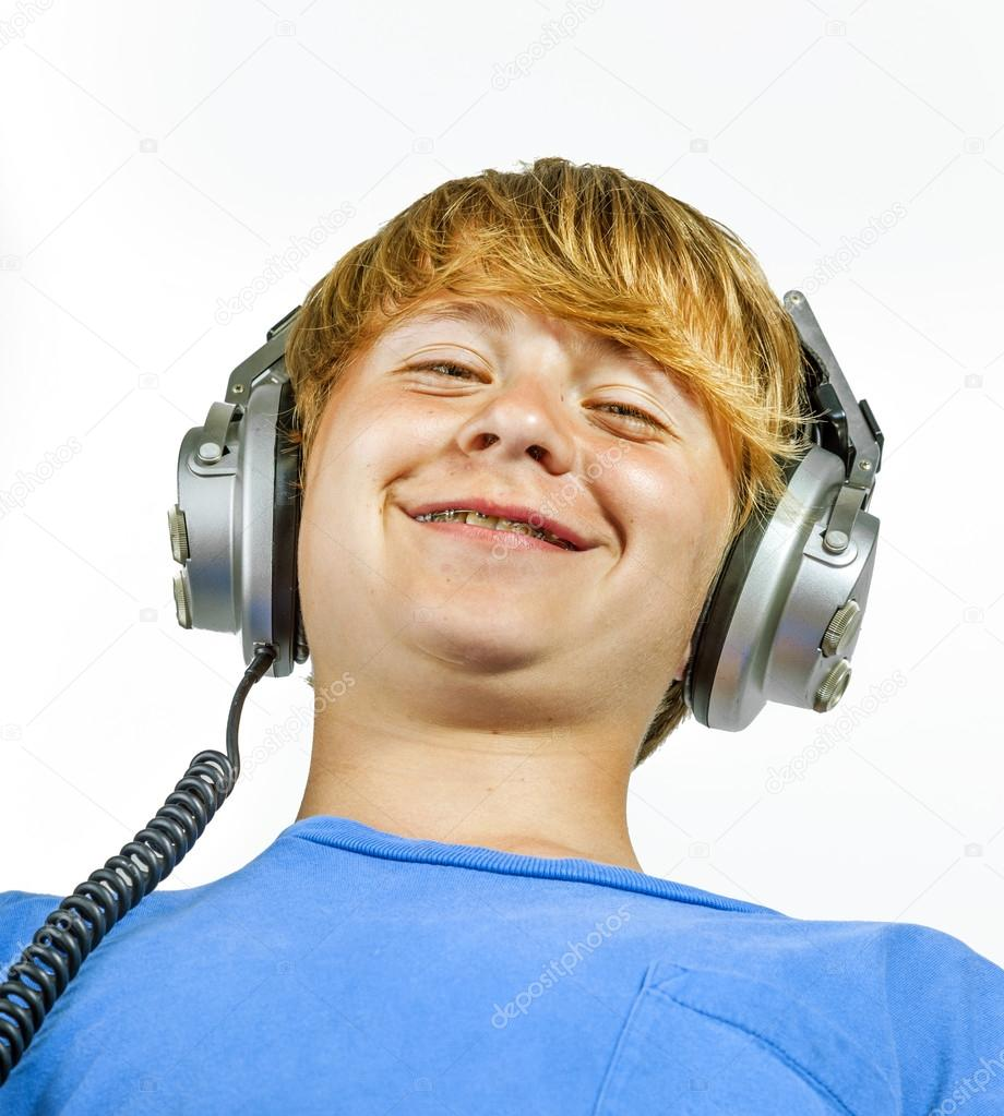 cute handsome boy listening to music by headphones