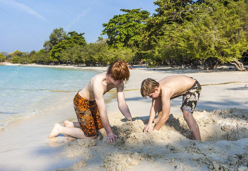 boys are playing at the  beach with sand and building figures