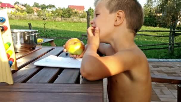 Malý chlapec jíst jablka a dělat domácí úkoly mimo