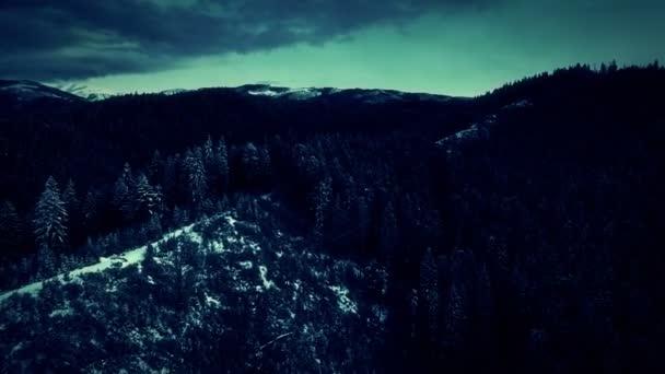 Letecký pohled na kopce a hory v zimě s bouřkovými mraky a blesky