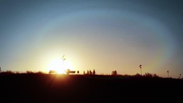 Siluette a piedi nel Parco della gente, sole splendente dietro