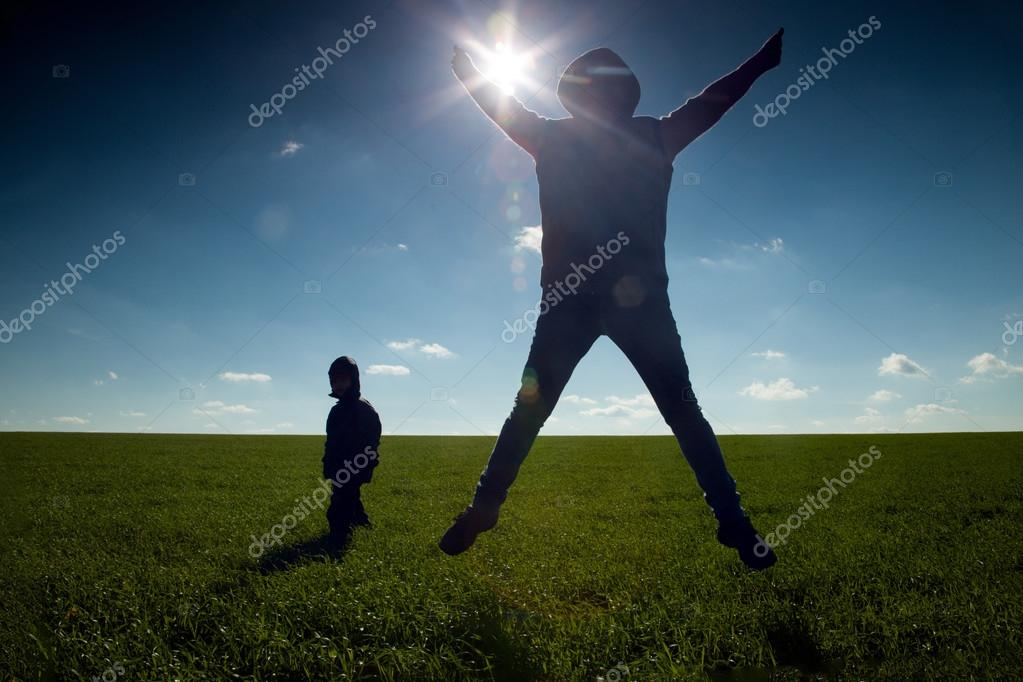 family outdoor jump on sunset background