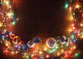 Fényképek A karácsonyfa számára füzérek lámpák egy fából készült háttér