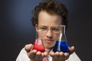boy studying a substance in a retort