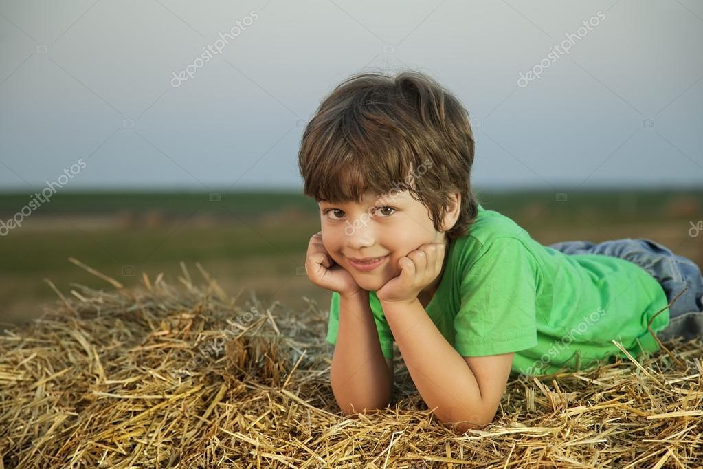 boy in a haystack in the field