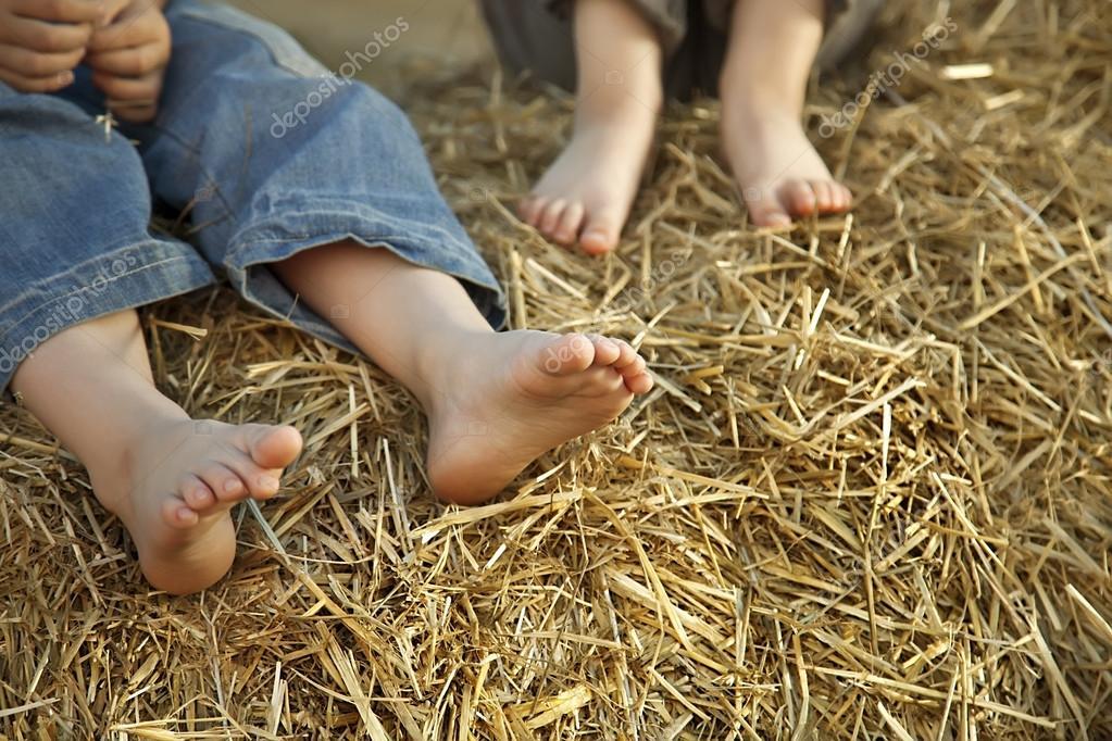 children's feet in the hay