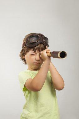 boy looks through a telescope