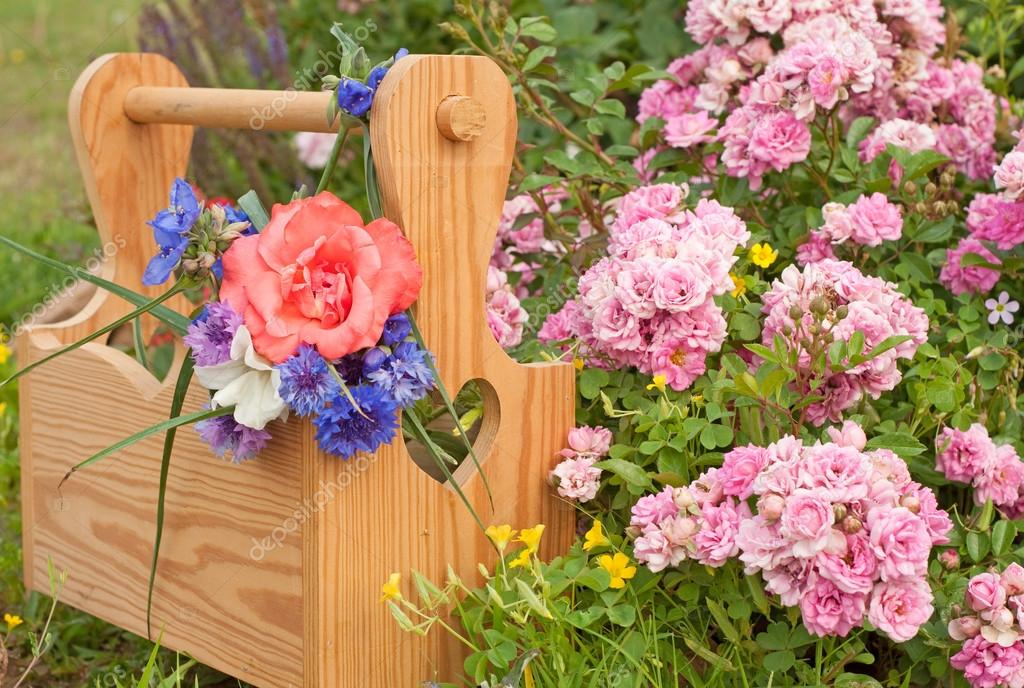 A wooden carrier box with spring flowers, against floral background with pink mini roses