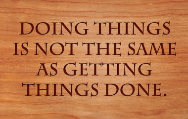 Doing things is not the same as getting things done - quote on wooden red oak background