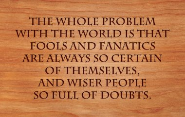 The whole problem with the world is that fools and fanatics are always so certain of themselves, and wiser people so full of doubts - quote on wooden red oak background