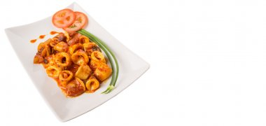 Malaysian dish of fried squid with hot and spicy sambal ot chili gravy with scallion and tomatoes on white plate.