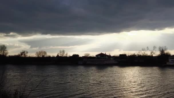 landscape with sunset on the river. sun through the clouds. rays of the sun and water. evening rainy landscape.