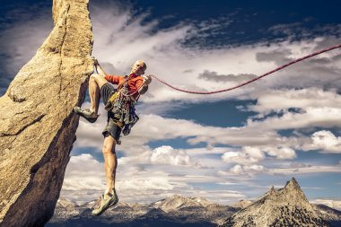 Male climber dangles from a sheer rock spire. stock vector