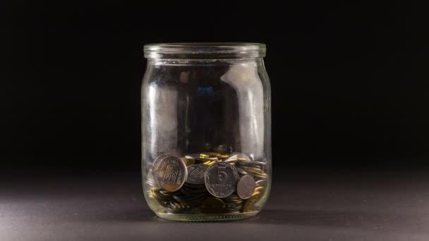 Zanikla z padající mince v Jar na černém pozadí. 4 k Ultra Hd