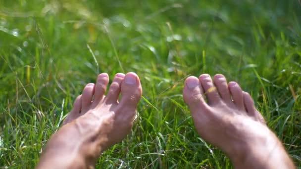 Bosé nohy na zelené trávě pohybující se prsty