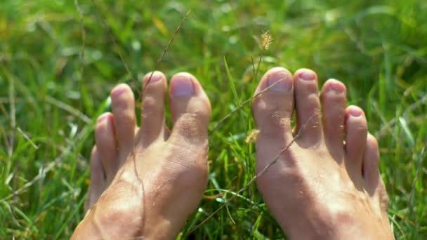 Barfuß auf dem grünen Gras die Finger bewegen