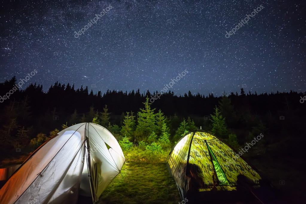 Illuminated camping tent under stars at night