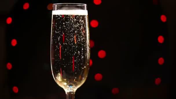 Bubliny uvnitř sklenku šampaňského na pozadí svátek světel