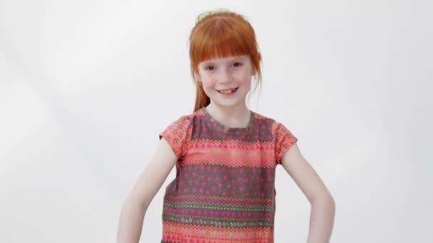 Little ginger girl showing thumb up gesture, turning, spinning around and smiling
