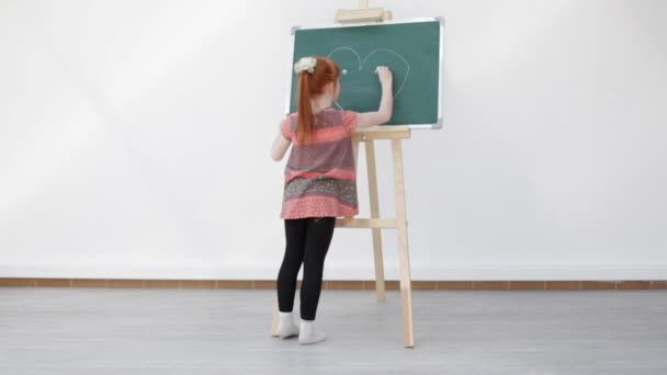 The little red-haired girl with freckles draws heart on the blackboard