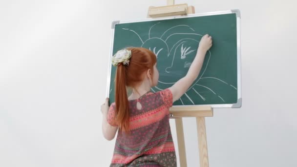 The little red-haired girl with freckles draws the sun in the form of heart on the board, making the inscription at the top