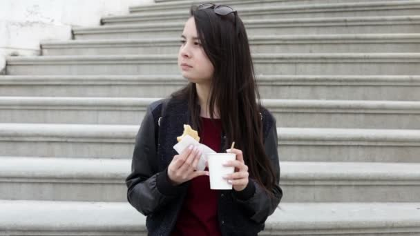 Close up young brunette woman in the city eating a sandwich