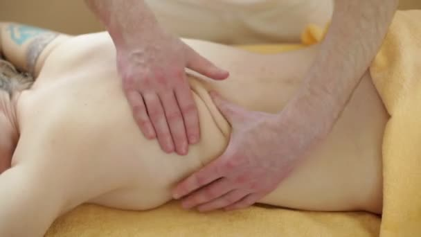 Massage. Manual therapist manipulates on woman's back