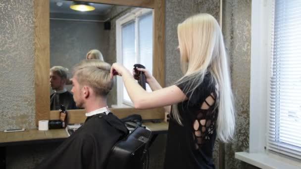 Woman barber making mans haircut