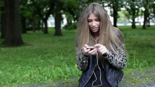 Mobile. Young blonde woman is listening to music
