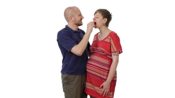 The man kissing pregnant woman, feeding her.